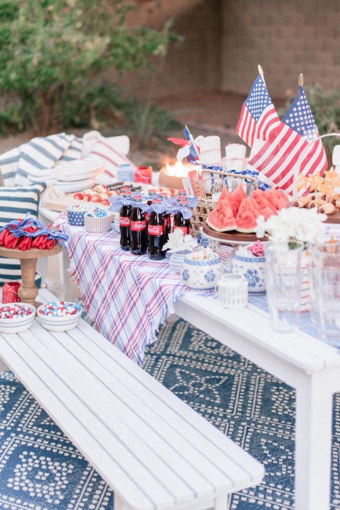 bench and table decorated with american flags fourth of july decorations different food and drinks on it