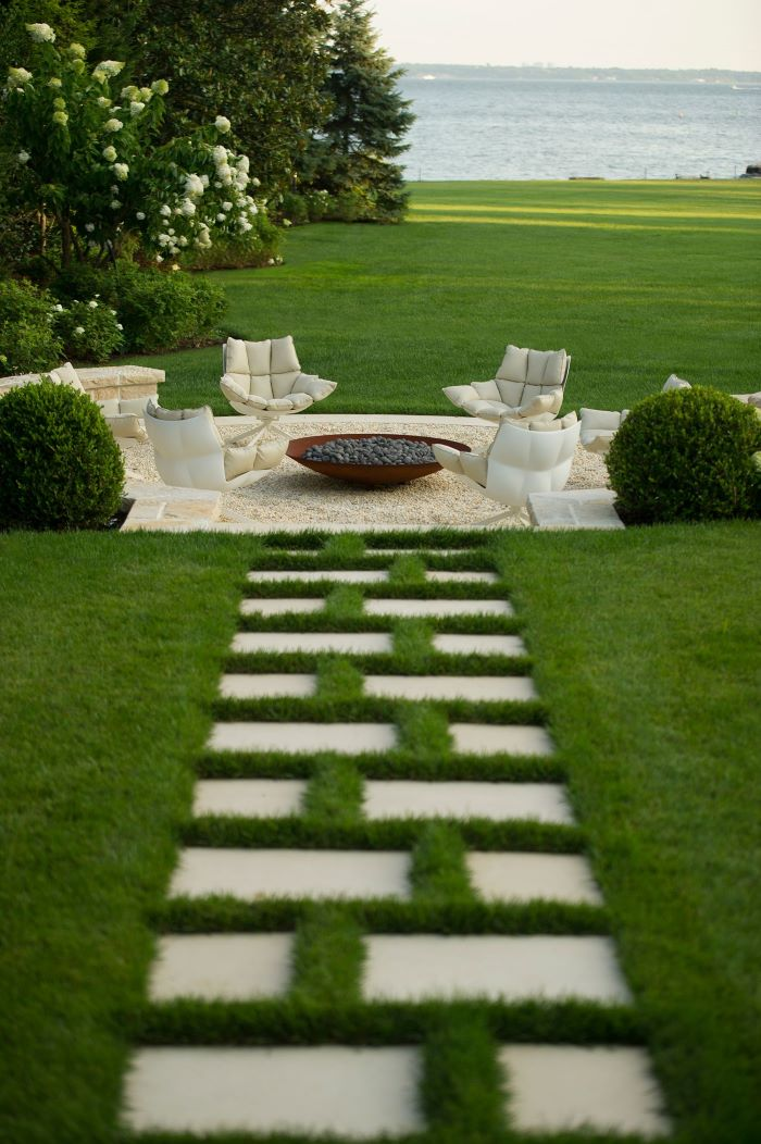 bench made of stones lounge chairs with white cushions arranged around homemade fire pit made of metal and rocks