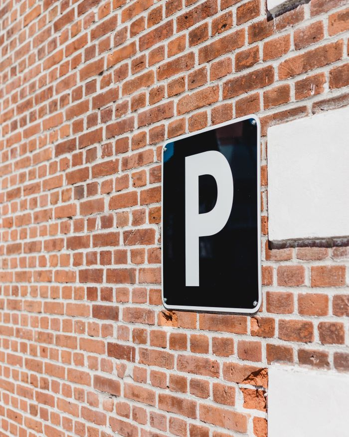 black parking sign hanging on brick wall parking spot in the city