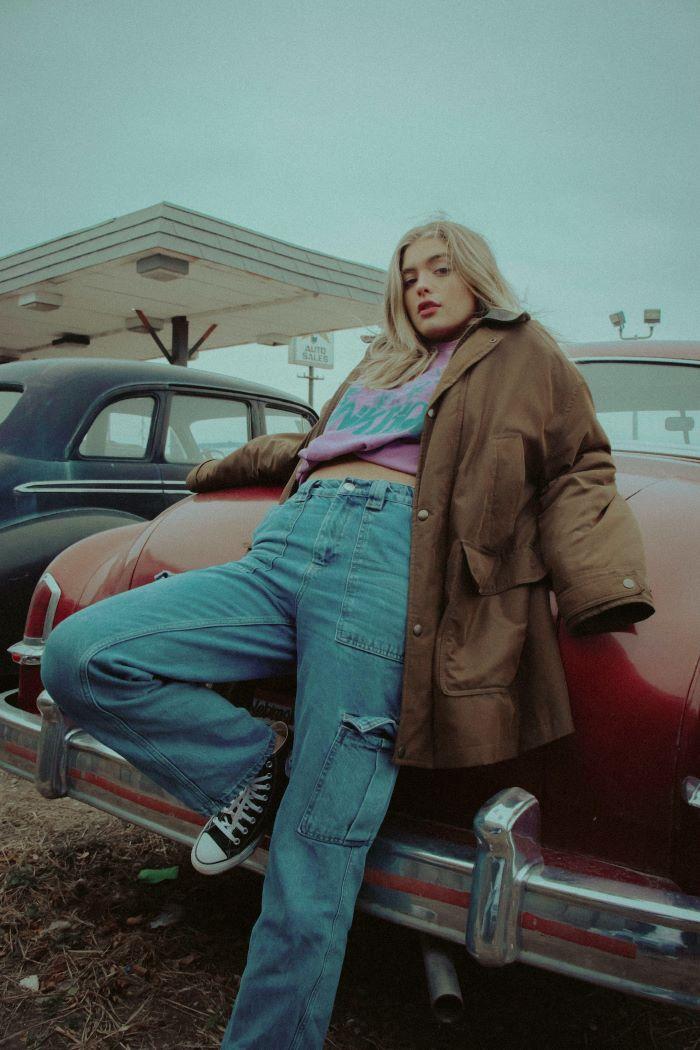blonde girl leaning on car women fashion for summer 2021 wearing oversized jacket jeans purple swetshirt