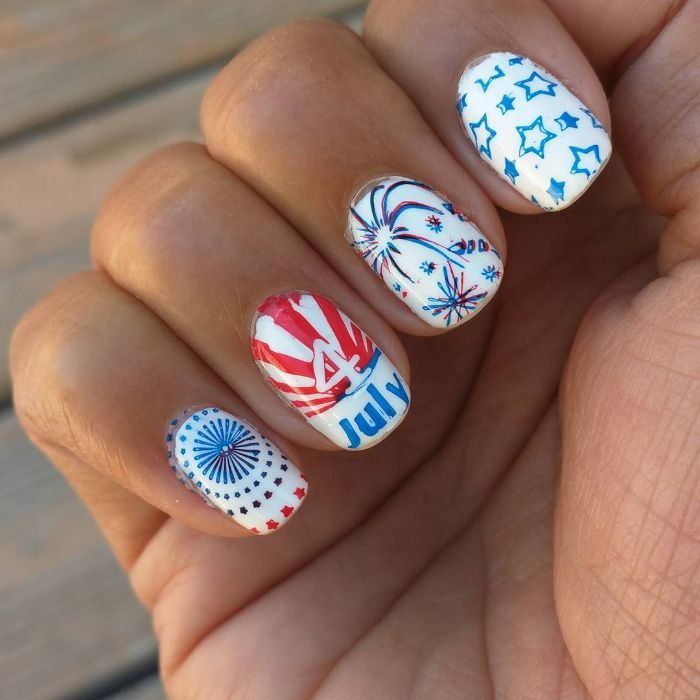 blue and red stars and fireworks 4th of july nails drawn on white nail polish base