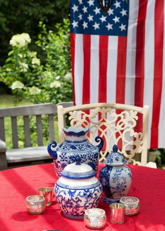 blue and white vintage vases jars in the middle of table patriotic decorations american flag in the background