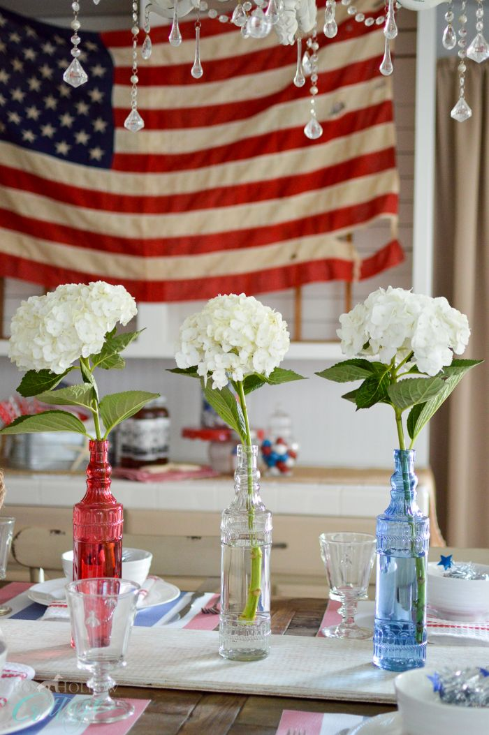 blue white red vases in the middle of the table 4th of july crafts american flag in the background