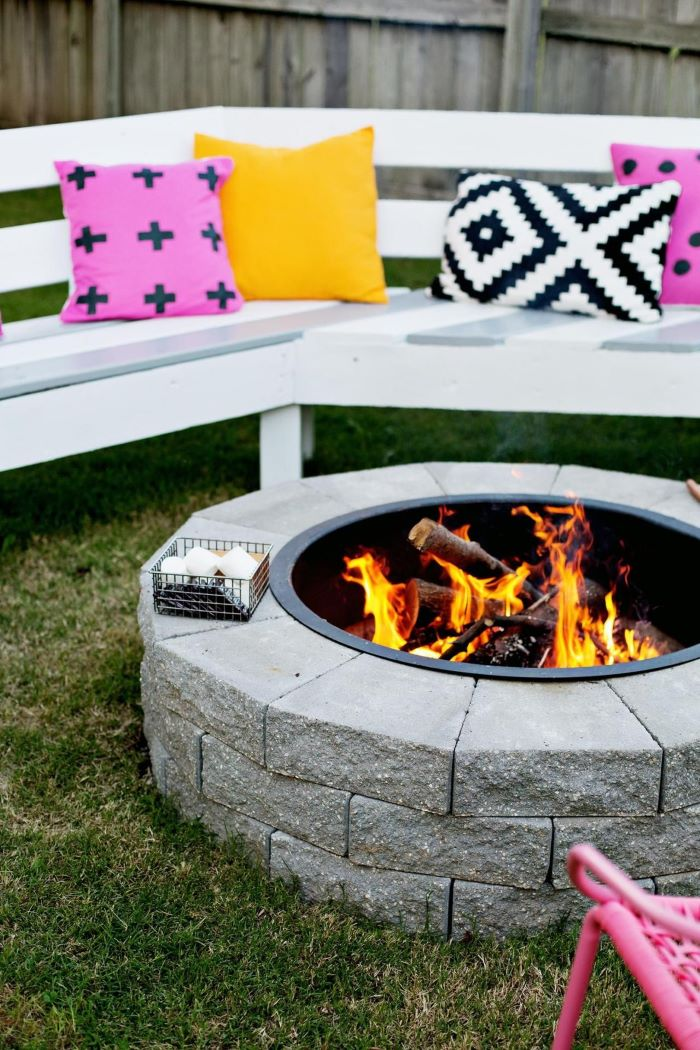 build your own fire pit made of stones white wooden bench with colorful throw pillows around it