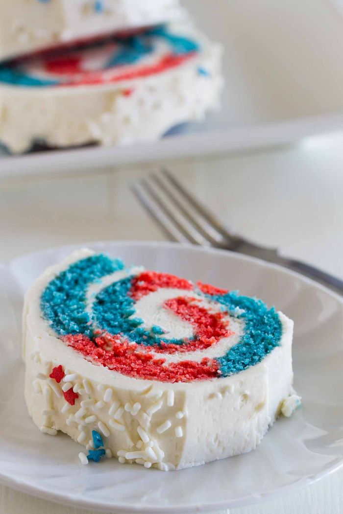 cake roll with red and blue in the middle white frosting on top 4th of july desserts red white and blue sprinkles