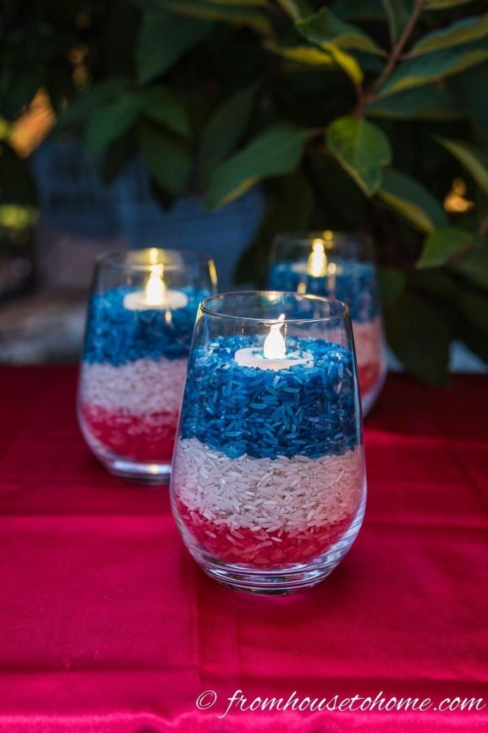candleholders filled with rice dyed in red white and blue diy 4th of july decorations placed on red table cloth