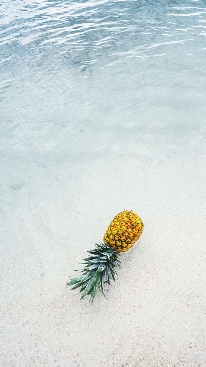 close up photo of pineapple beach aesthetic wallpaper laying on the beach in the water