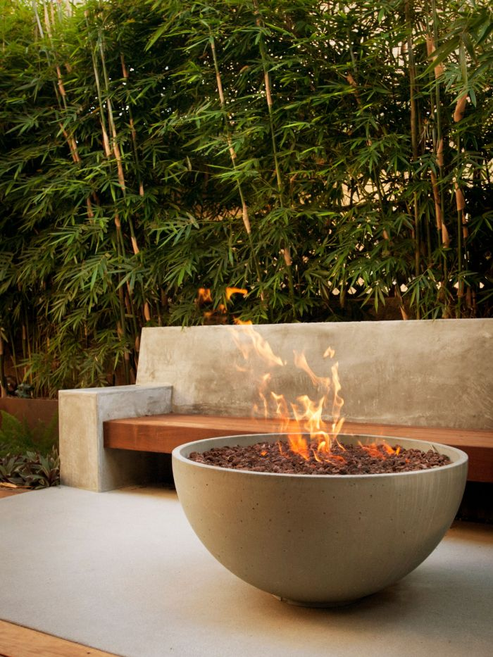 concrete bowl filled with rocks fire burning inside how to make a fire pit bench next to it made of stone and wood