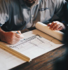 construction business ideas man sitting at table architect plans in front of him