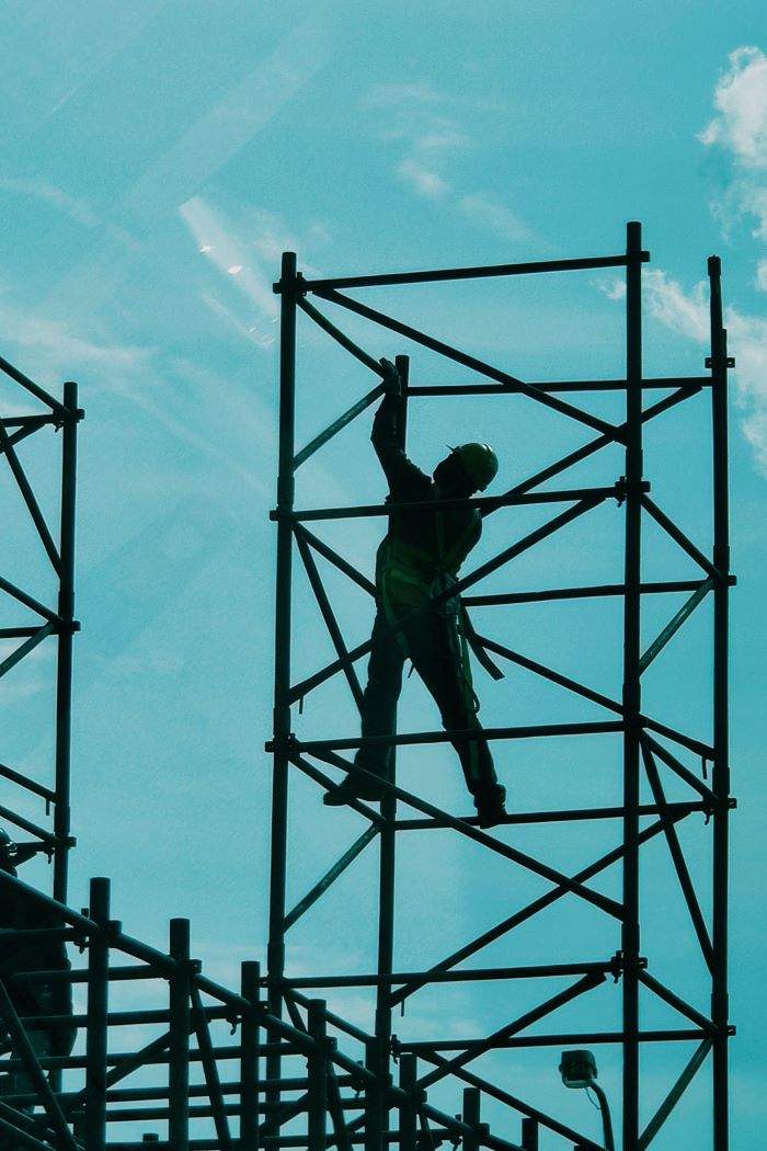 construction worker standing on metal railing construction business ideas blue sky behind him