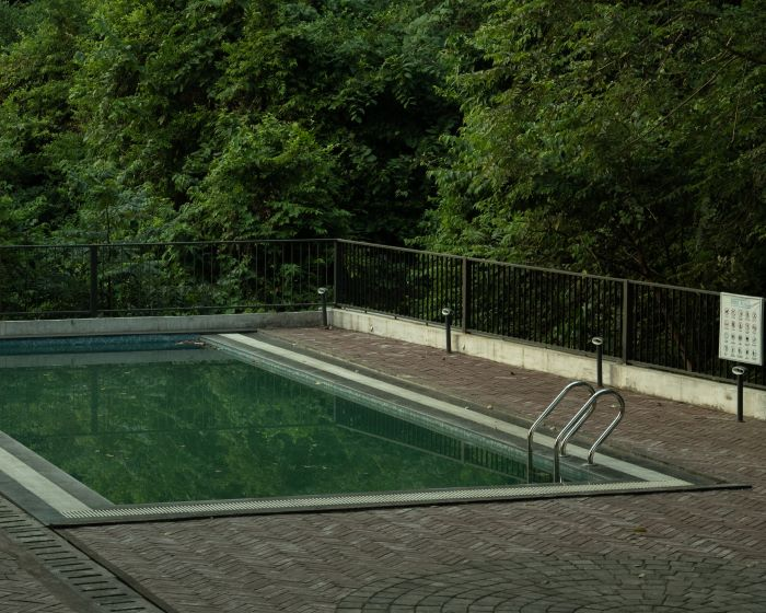 dirty pool with ladder installing a swimming pool surrounded by tiled floor with fence trees around it