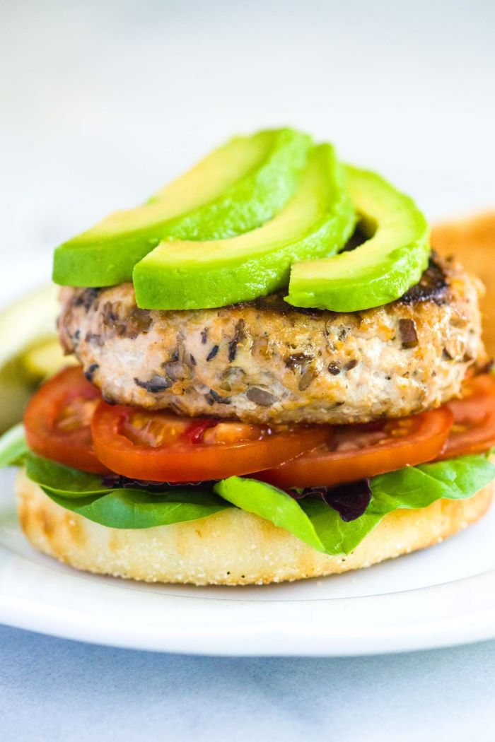 easy hamburger recipes turkey burger with tomatoes lettuce avocado placed on white plate