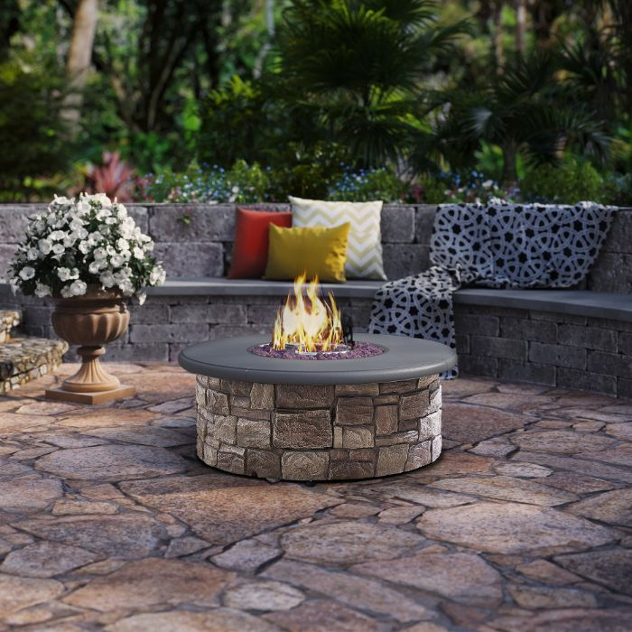 fire burning in round outdoor fire pit ideas made of stone next to bench with throw pillows blanket