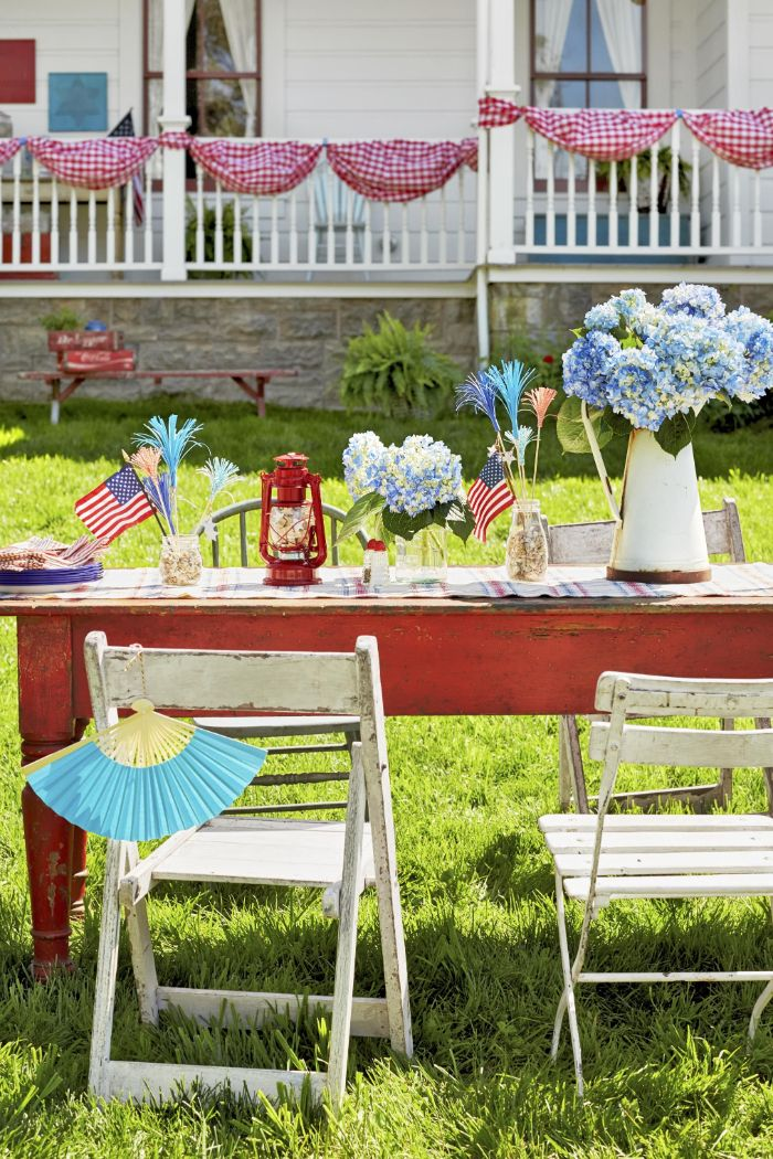 fourth of july crafts wooden table and chairs in the backyard decorated with american flags blue flowers
