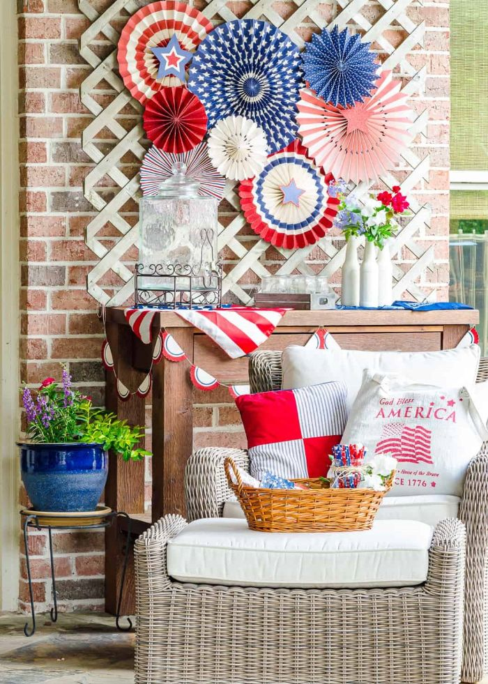 fourth of july decorations paper fans in red white blue with stars stripes hanging above garden furniture