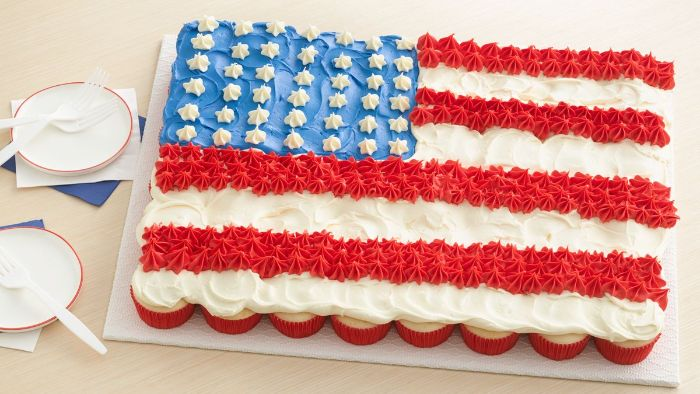 fourth of july desserts cupcakes arranged on platter decorated in red white blue frosting as the american flag