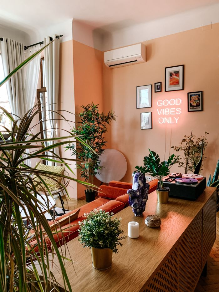 good vibes only neon sign photos around it décor ideas for living room lots of plants in the living room