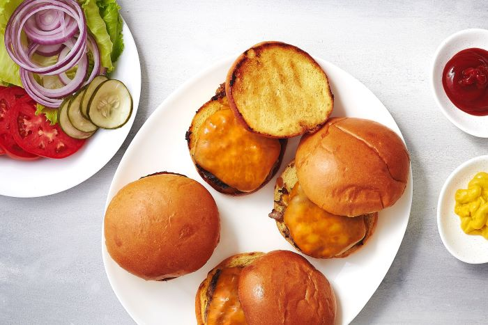 how to layer burgers homemade burgers buns patties melted cheese ingredients on plate on the side