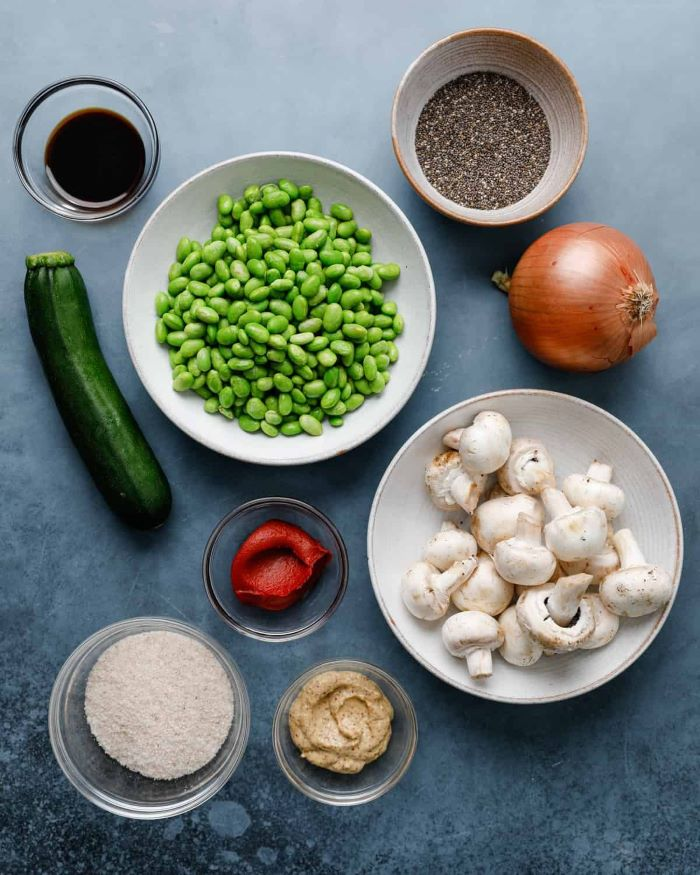ingredients for veggie burger placed in bowls plates how to make hamburgers placed on granite surface