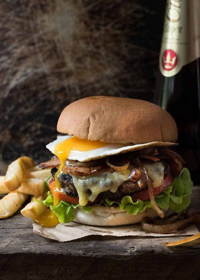 juicy burger with melted cheese egg tomatoes lettuce grilled onions bacon homemade burgers