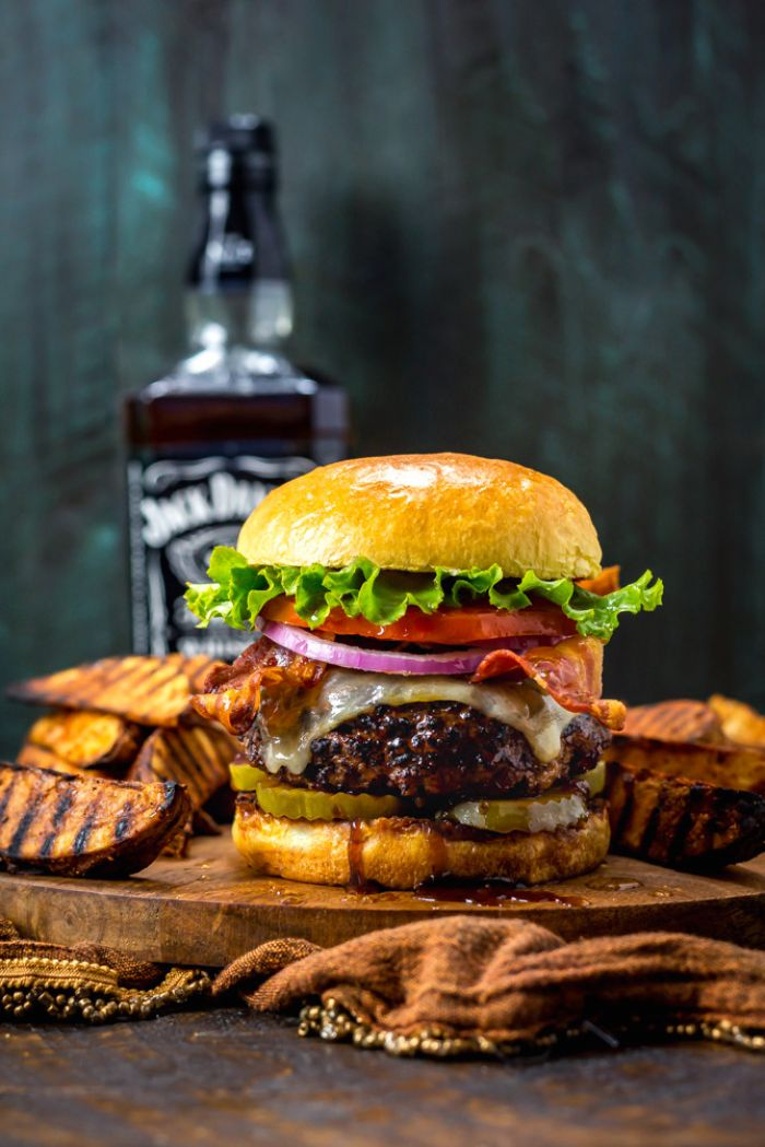 large burger with cheese bacon onions tomatoes lettuce hamburger recipes placed on wooden board