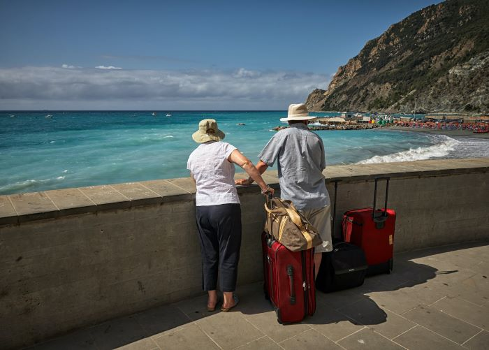 man and woman leaning on balcony overlooking the ocean travel tips suitcases bags next to them