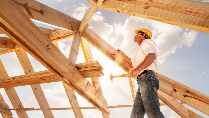 man waring safety hat goggles holding a hammer building your own house standing on the wooden foundations of house