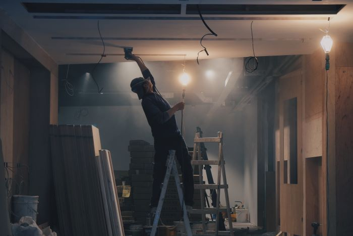 man wearing protective gear on top of ladder construction business ideas working on ceiling