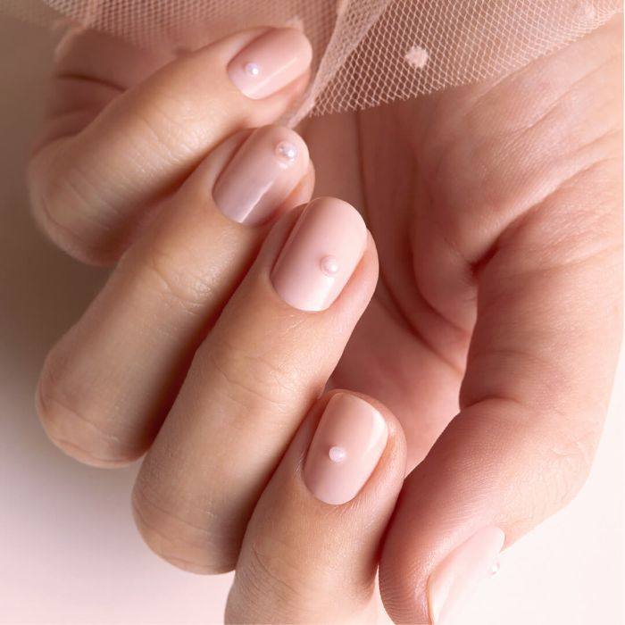 nude nail polish decorated with small white pearl on each finger summer nails 2021