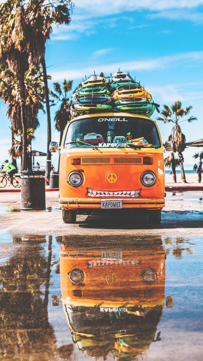 orange van with surfs on it parked next to the beach best summer wallpapers