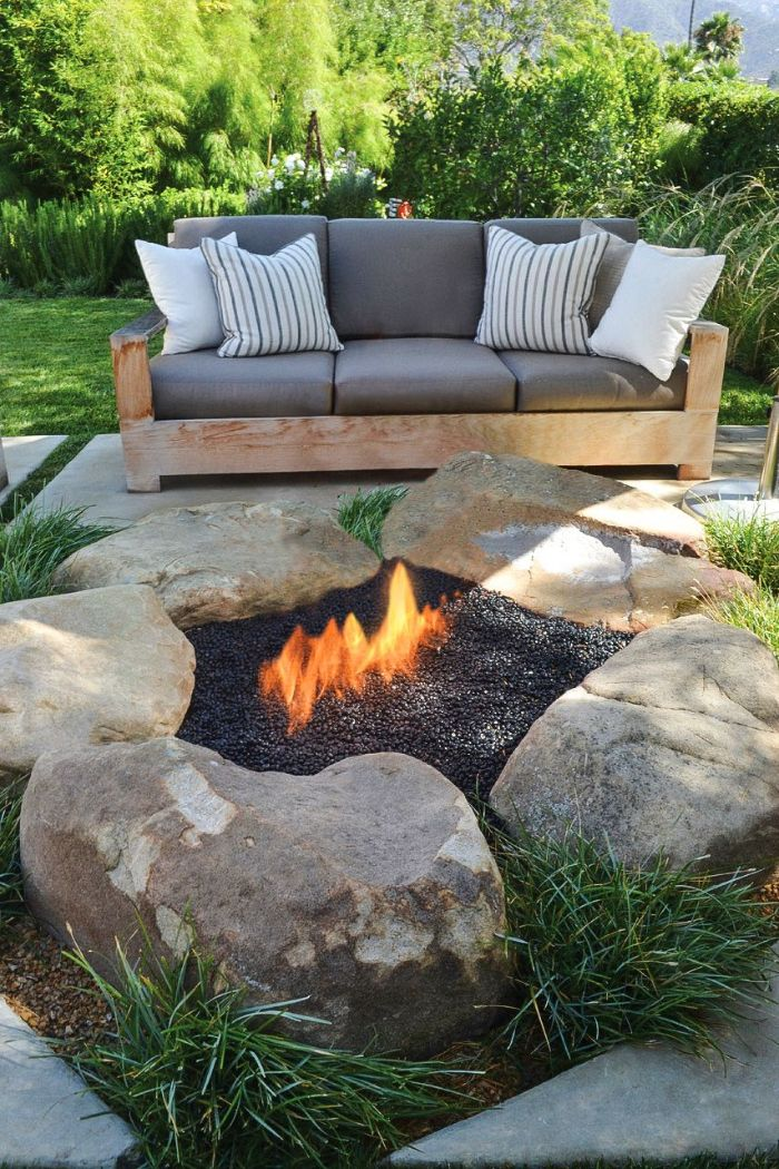 outdoor fire pit ideas five large rocks arranged in circle filled with gravel wooden sofa with gray cushions