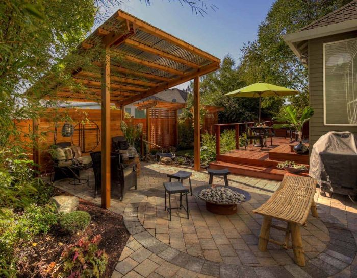 pergola with garden furniture underneath in ground fire pit small stools arranged around metal fire pit filled with stones