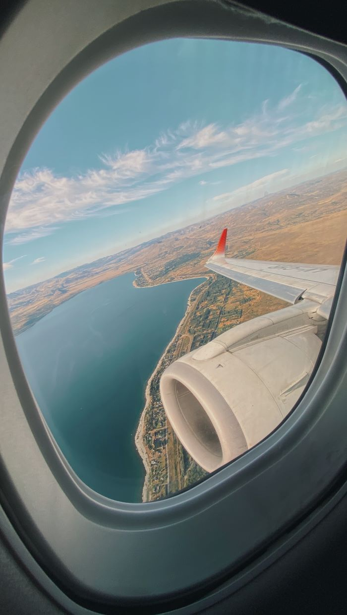 photo taken through the window of plane travel tips wing of the plane visible
