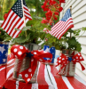 potted red flowers flags inside the pots 4th of july decorations blue red ribbons tied around them