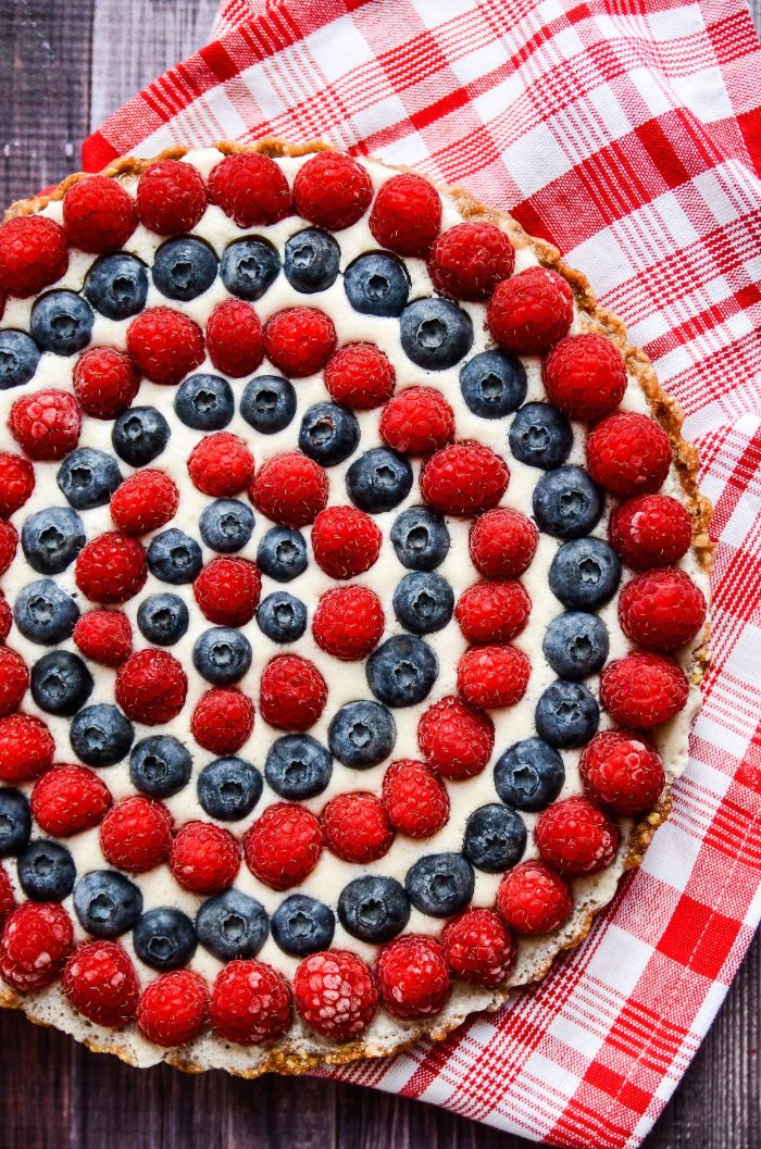 raspberry blueberry tart decorated in circles 4th of july recipes red and white cloth under it