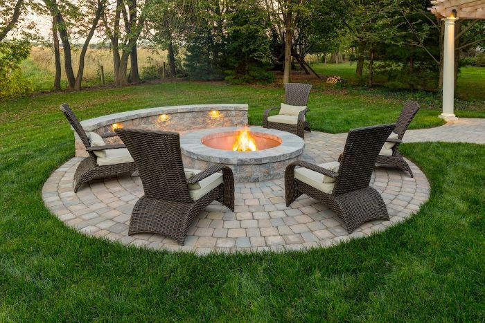 rattan furniture arranged around round fire pit made of stone fire pit seating ideas