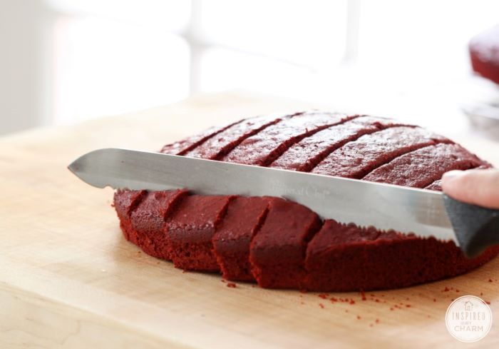 red velvet cake being cut into small bites with knife traditional 4th of july foods on wooden cutting board