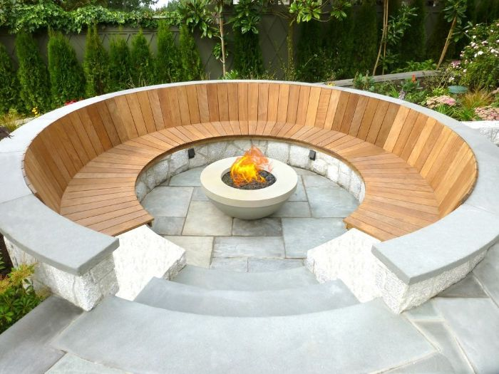 round wooden bench around concrete bowl filled with rocks how to make a fire pit fire burning inside