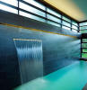 tabletop fountain wall covered with black stone bricks fountain flowing down into pool