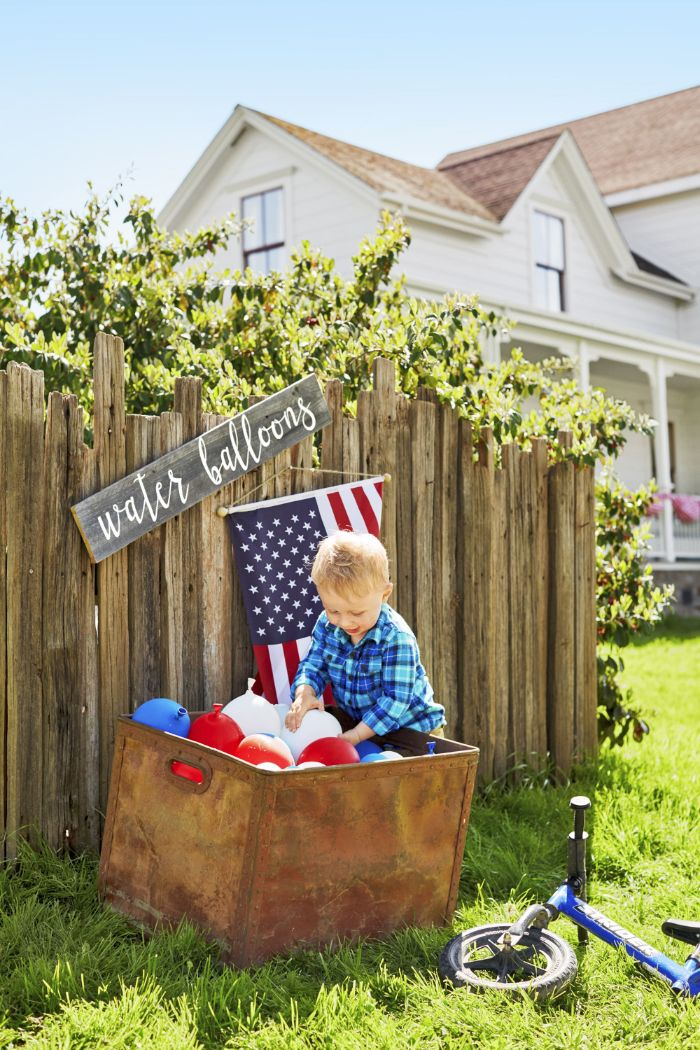 toddler taking out water balloons from crate fourth of july decorations red white and blue balloons