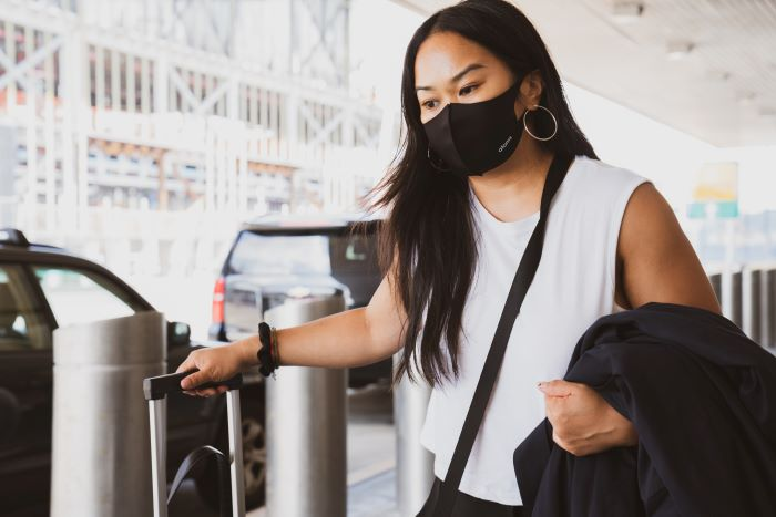 travel tips woman with long black hair wearing white top face mask carrying luggage