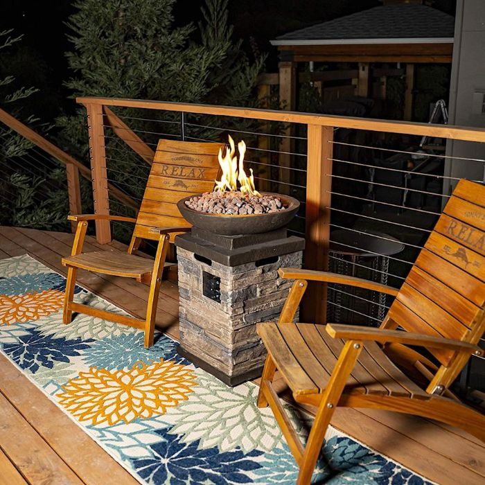 two wooden chairs on rug with orange blue flowers backyard fire pit ideas standing concrete bowl with rocks