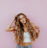 woman with very long blonde wavy hair avoid bad hair days wearing white crop top jeans