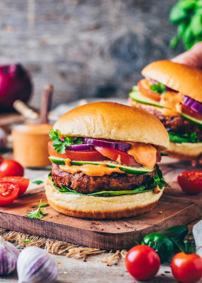 wooden board best hamburger recipe burger with lettucecucumbers tomatoes onions cheese parsley garnish