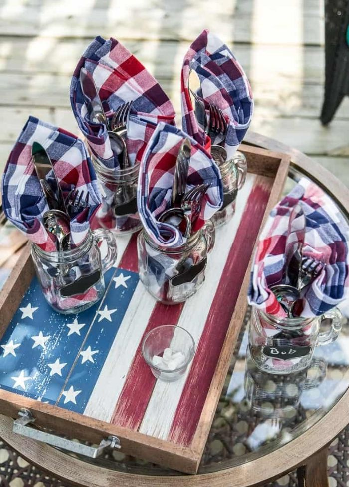 wooden board with american flag painted on it 4th of july decorations red white blue napkins inside jars with fork spoon knife