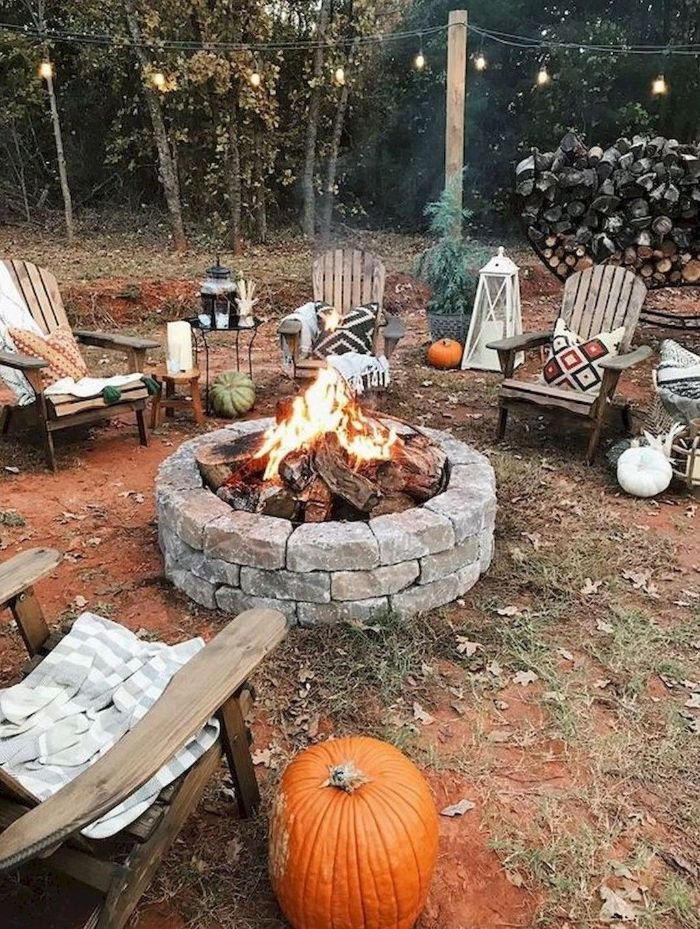 wooden lounge chairs around backyard fire pit ideas made from rocks lanterns and pumpkins around it