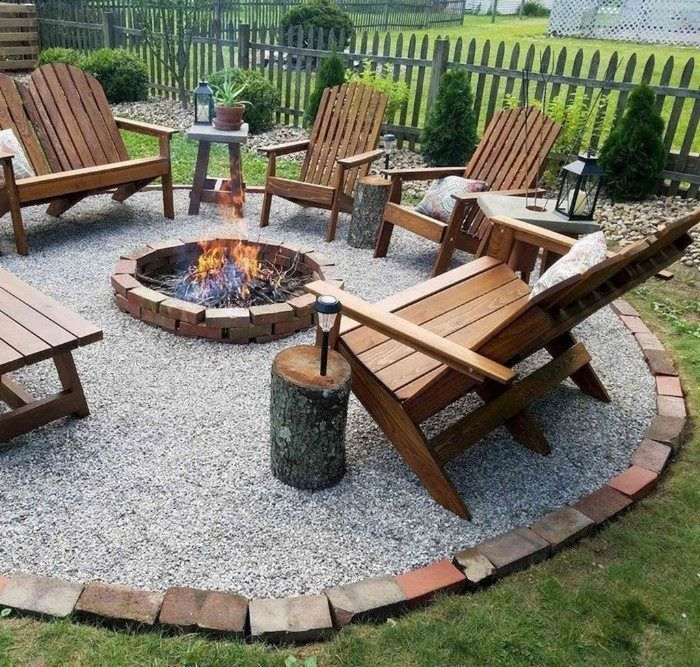 wooden lounge chairs arranged in circle around backyard fire pit ideas placed on gravel