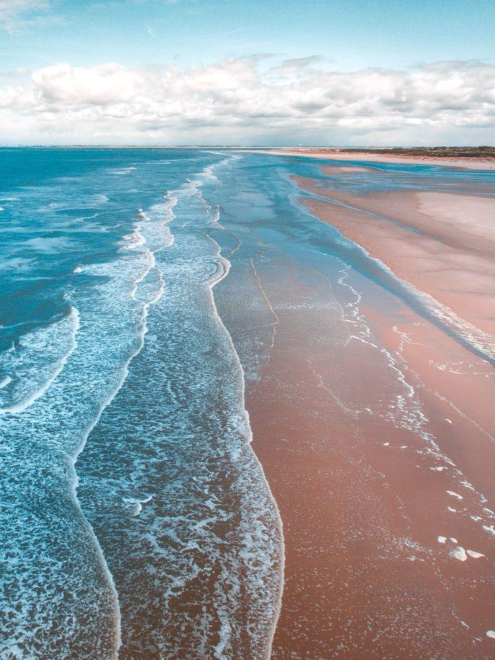 aerial photo of waves crashing into empty beach with sand beach desktop wallpaper