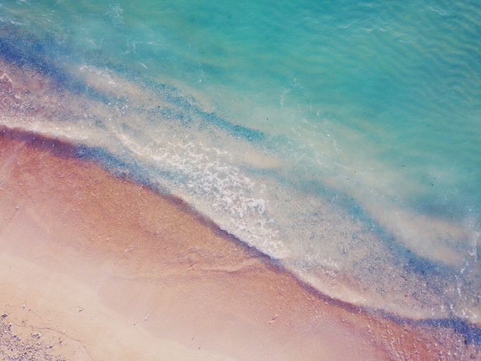 beach aesthetic wallpaper blue waves crashing into a sandy beach with small rocks