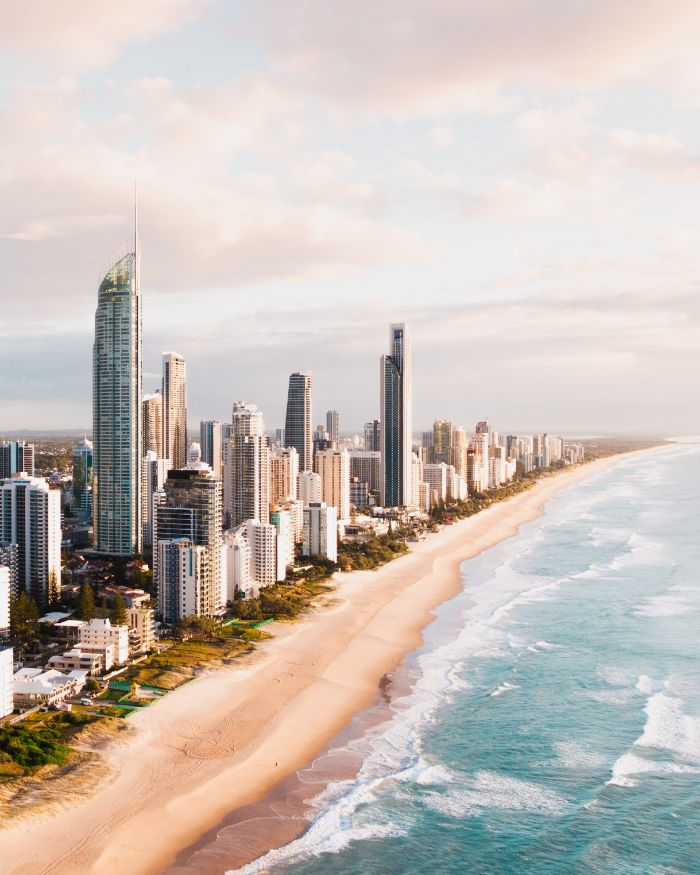 beach background hd tall buildings skyscrapers on beach waves crashing into it aerial view